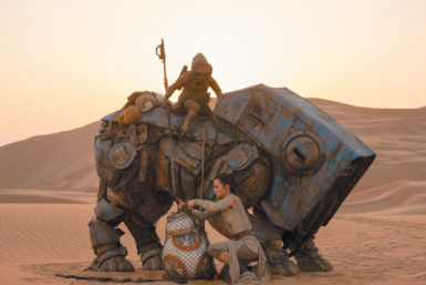 Rey (Daisy Ridley) freeing the droid BB-8 from the net of the scavenger Teedo and his semi-mechanical Luggabeast in Star Wars: The Force Awakens