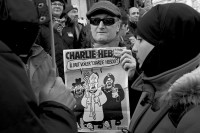 """A demonstrator with an issue of Charlie Hebdo at the march against terrorism, Paris, January 11, 2015. The cartoon on the cover shows a Jew, a Catholic, and a Muslim demanding that '""""Charlie Hebdo"""" must be veiled!'"""