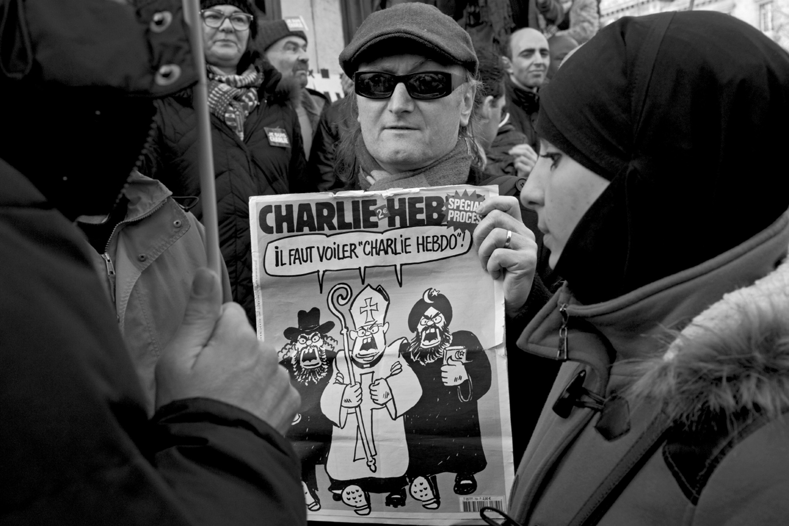 "A demonstrator with an issue of Charlie Hebdo at the march against terrorism, Paris, January 11, 2015. The cartoon on the cover shows a Jew, a Catholic, and a Muslim demanding that '""Charlie Hebdo"" must be veiled!'"