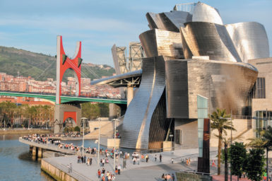 The Guggenheim Museum in Bilbao, Spain, designed by architect Frank Gehry. At left are the Nervión River and La Salve Bridge, adorned with Daniel Buren's artwork Red Arches (2007), commissioned for the museum's tenth anniversary.