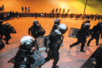 Riot police retreating after trying to push back protesters near the Cabinet of Ministers building during the Maidan protests in Kiev, December 2013