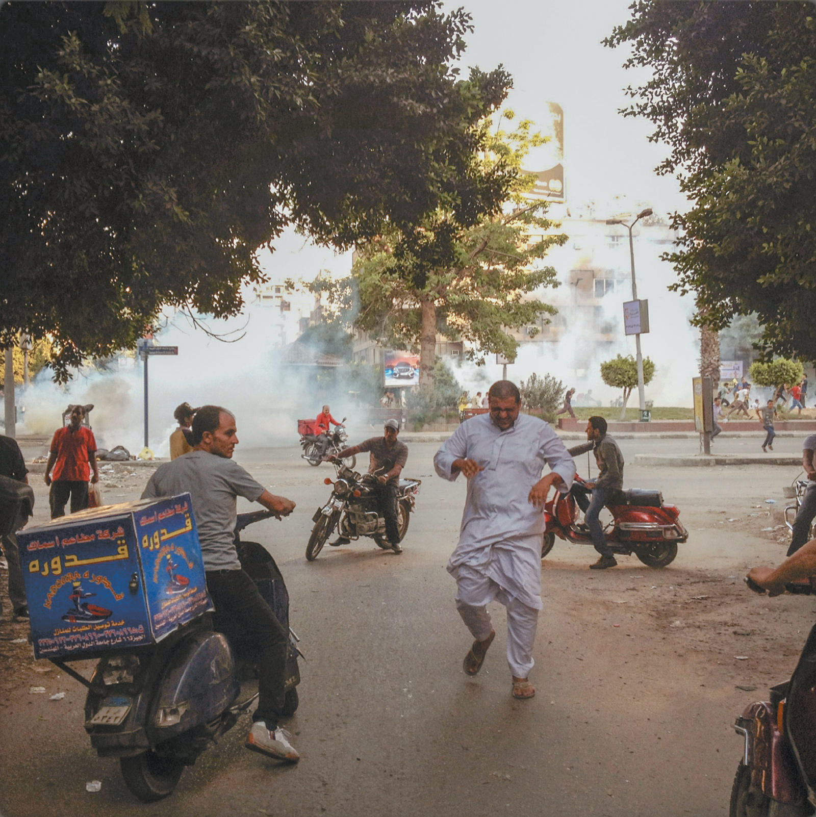 Police officers throwing tear gas at participants in a rally for the Muslim Brotherhood, Cairo, August 2013