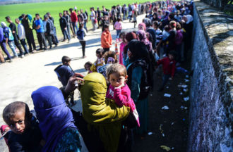 Migrants wait in line for food in a makeshift camp at the Greek-Macedonian border, March 31, 2016