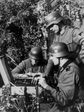 German soldiers in the field enciphering a message on the Enigma code machine, circa 1940