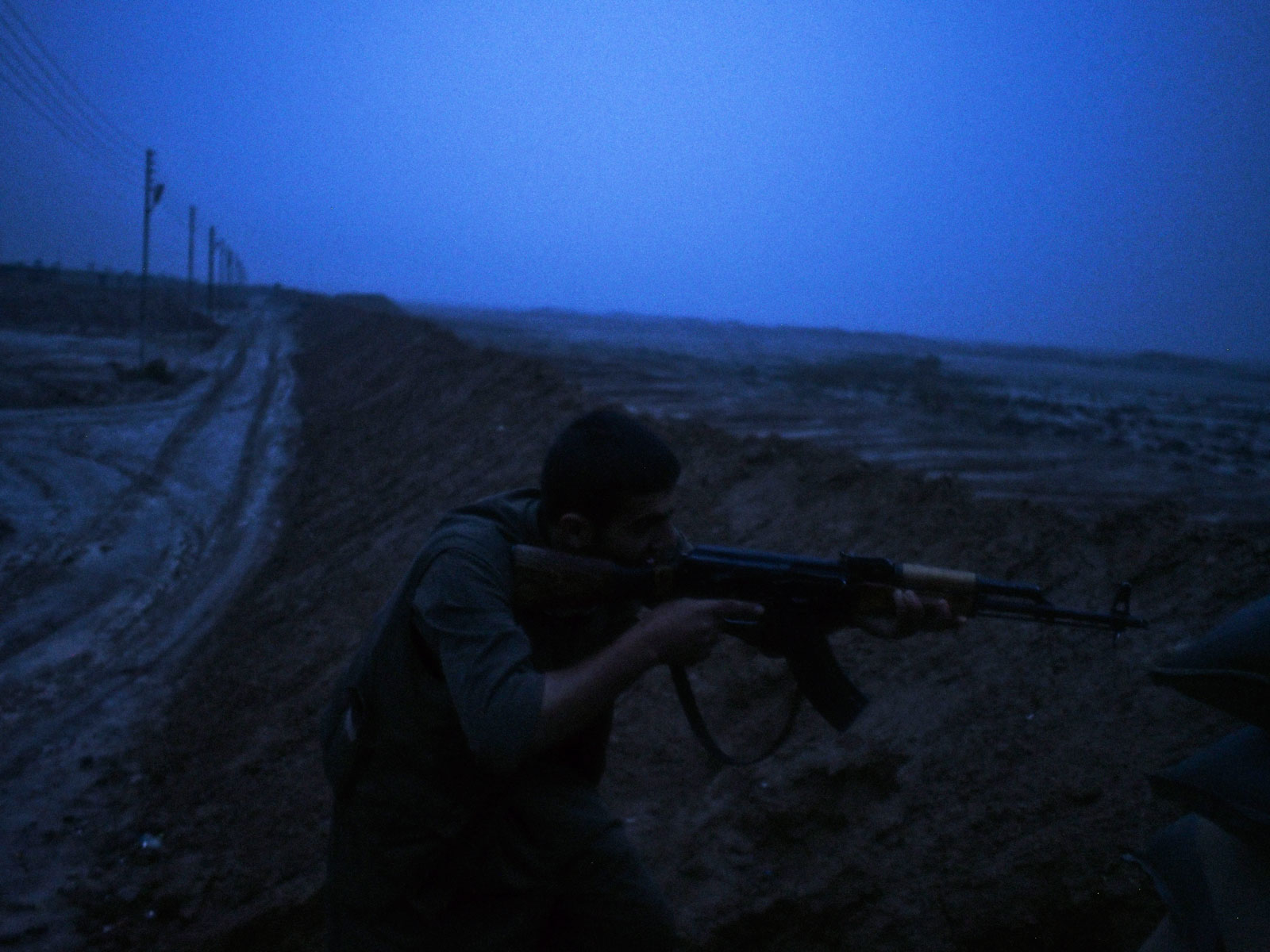 A Kurdish PKK fighter aiming his rifle at an Islamic State position, Dokuk, Iraq, December 3, 2014