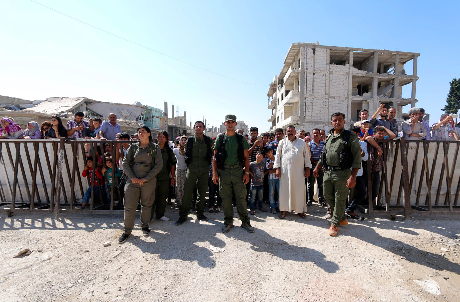 Kurdish Security Forces (Asayish) secures a road as residents watch ambulances carrying the bodies of the two Syrian toddlers and their mother, who drowned while trying to reach Greece, at the border town of Kobani, Syria, September 4, 2015