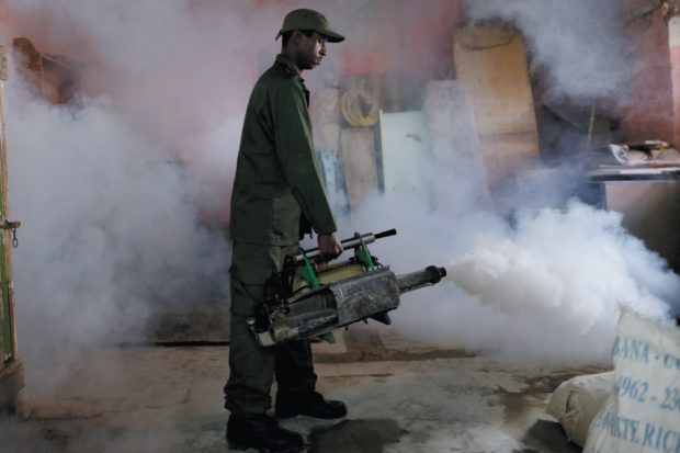 A military reservist fumigating a house as a preventive measure against the Zika virus and other mosquito-borne diseases, Havana, Cuba, March 2016