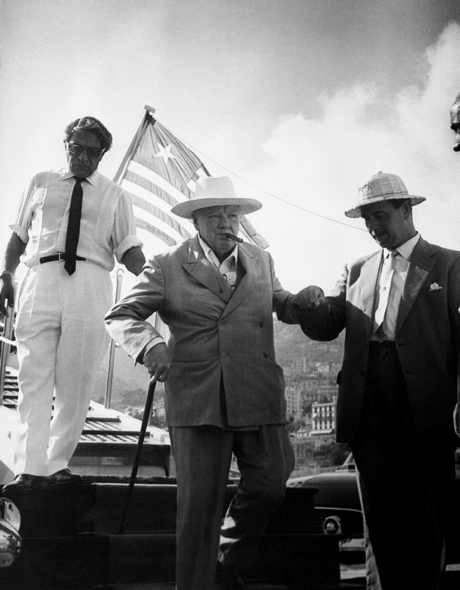 Winston Churchill being helped off Aristotle Onassis's yacht Christina by Onassis (left) and Churchill's bodyguard Edmund Murray, August 1959