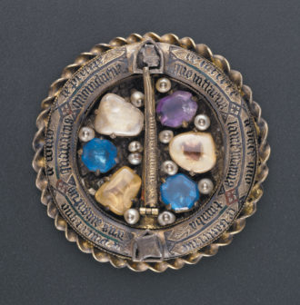 "A reliquary medallion from the court of Charles V of France, who reigned from 1364 to 1380. According to Cynthia Hahn in Saints and Sacred Matter, 'on the front of the object we see what looks like the back of a ring brooch. The thorn [from Christ's crown of thorns], identified in inscriptions as enclosed in the brooch's ""pin,"" is encircled by a tubular ring that also holds Passion relics and reinforces the idea of the Crown.'"