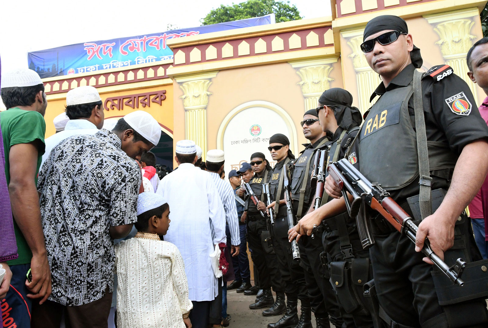 Muslims lined up for prayer with Bangladeshi security forces looking on, Dhaka, Bangladesh, July 7, 2016