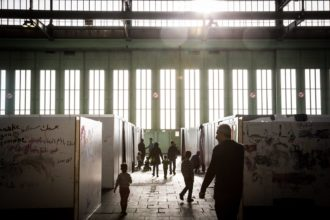 Refugees from Syria, Afghanistan, Iraq, and elsewhere in temporary housing at the former Tempelhof Airport, Berlin, February 2016