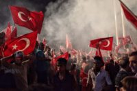 Supporters of Turkish President Tayyip Erdogan wave flags as they gather in Istanbul's central Taksim Square on July 18, 2016