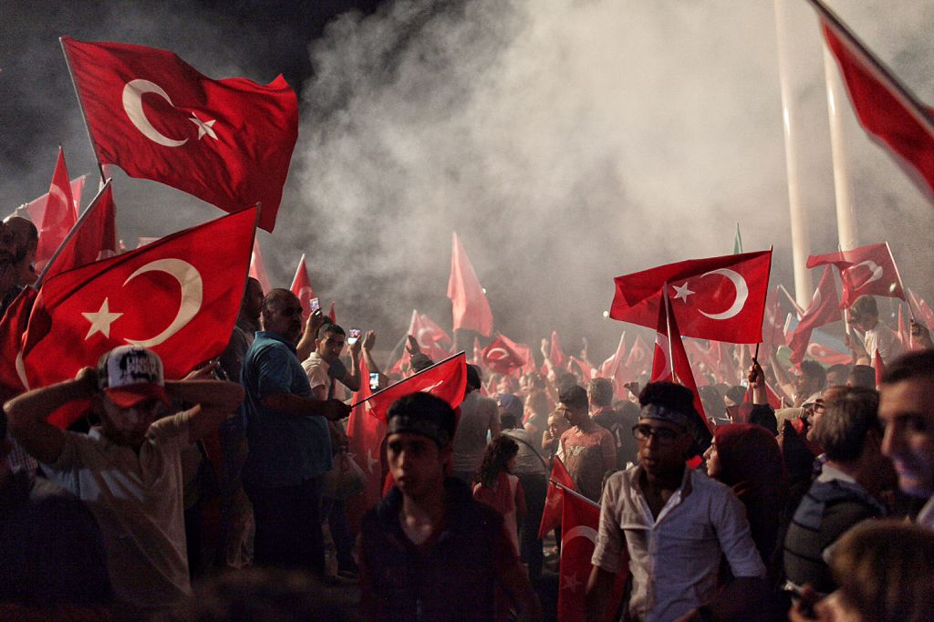 Supporters of Turkish President Recep Tayyip Erdogan wave flags as they gather in Istanbul's central Taksim Square on July 18, 2016
