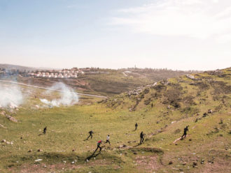 Palestinian protestors run from tear gas fired by Israeli soldiers at a weekly protest against the Israeli occupation, West Bank, Nabi Saleh, 2013