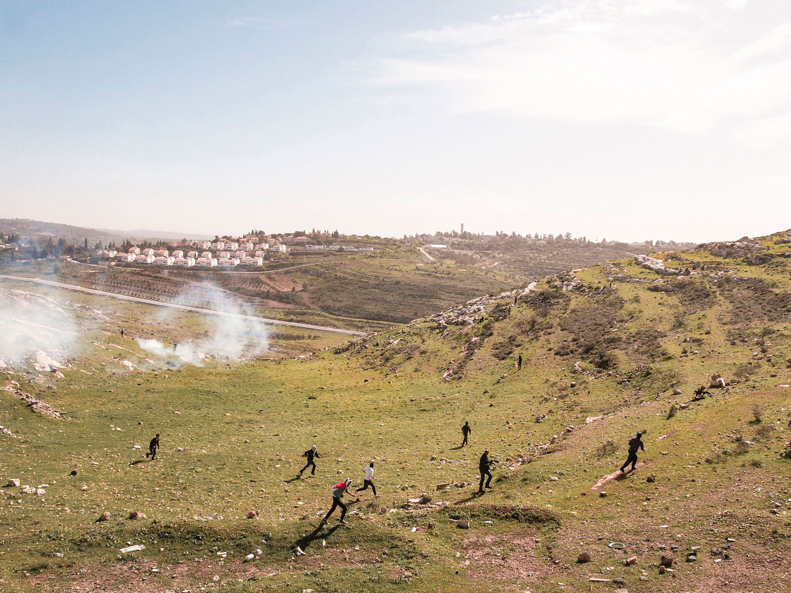 Palestinian protestors running from tear gas fired by Israeli soldiers at a weekly protest against the Israeli occupation, West Bank, Nabi Saleh, 2013