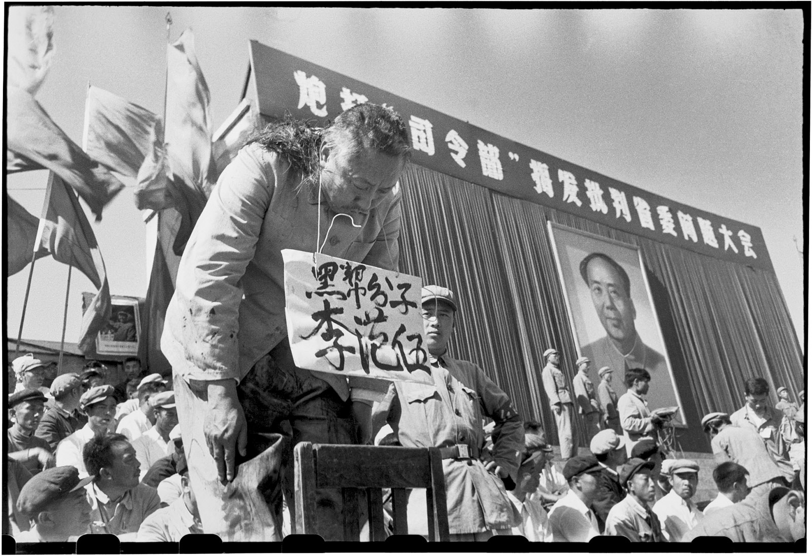 Li Fanwu, the governor of China's Heilongjiang province, being denounced and tortured at a rally in Red Guard Square, Harbin, August 1966. One of his alleged crimes was political ambition, evidence for which was found—according to the photographer Li Zhensheng's book Red-Color News Soldier (2003)—'in his hairstyle, which gave him an ill-fated resemblance to Mao and so was said to symbolize his lust for power.' Two Red Guards chopped and tore out his hair, after which he was made to bow for hours. The banner behind him reads, 'Bombard the Headquarters! Expose and denounce the provincial Party committee.'