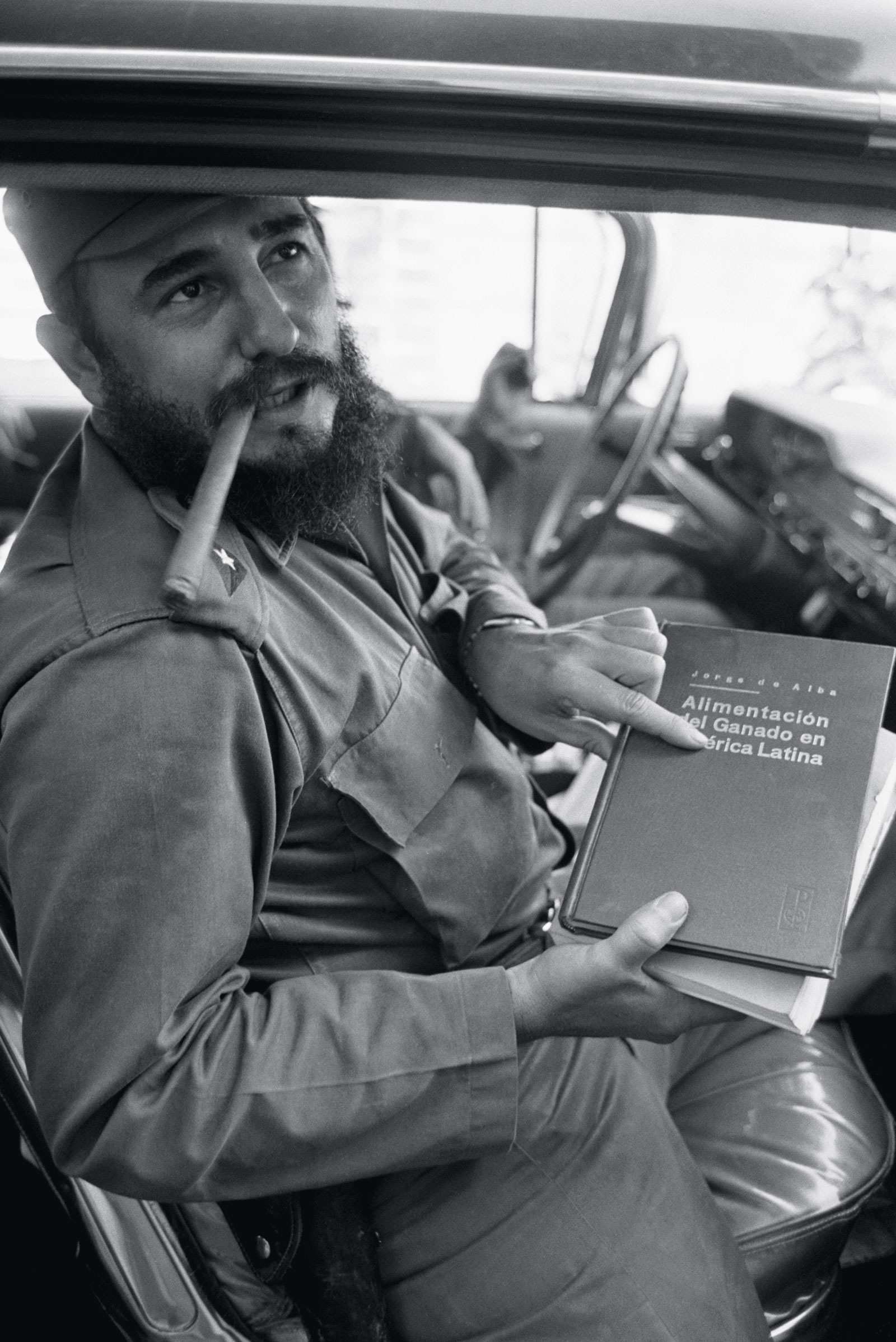Fidel Castro holding <em>The Feeding of Cattle in Latin America</em>, by Mexican author Jorge de Alba, 1964