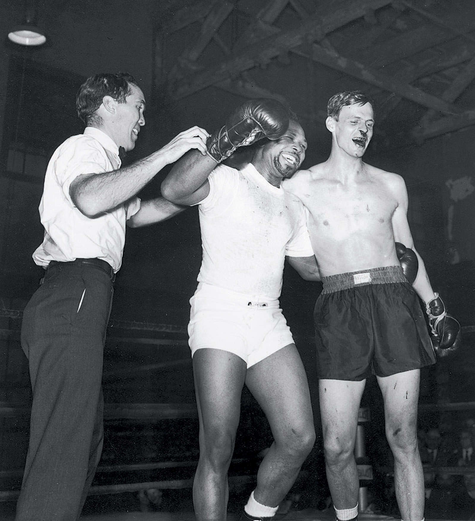 "George Plimpton, right, after a boxing match with Archie Moore at Stillman's Gym, New York City, 1959; Ezra Bowen, the Sports Illustrated editor who acted as referee, is at left. 'Quite visible are the effects Archie Moore left on the author's nose,' Plimpton writes in Shadow Box, 'what would have been described in the jaunty style of the mid-nineteenth century as follows: ""Archie dropped a hut'un on George's sneezer which shook his ivories and turned the tap on.""'"