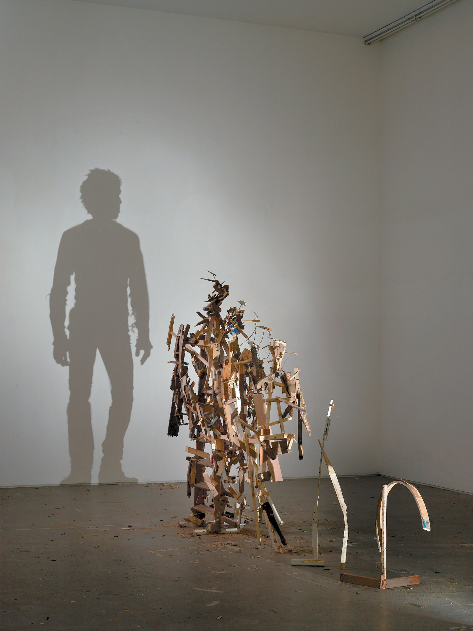 Tim Noble and Sue Webster: Self-Imposed Misery, 2010, a sculpture in which a two-dimensional human silhouette emerges from the projection of a more complicated three-dimensional array. Analogously, according to Jim Holt and others, the mystery of quantum nonlocality suggests that the three-dimensional space we experience might be a projection of a higher-dimensional reality in which the concept of distance is radically different.