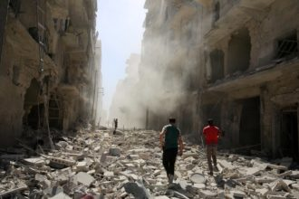 Syrians inspecting the damage after an air strike on the al-Qaterji neighborhood of Aleppo, September 2016