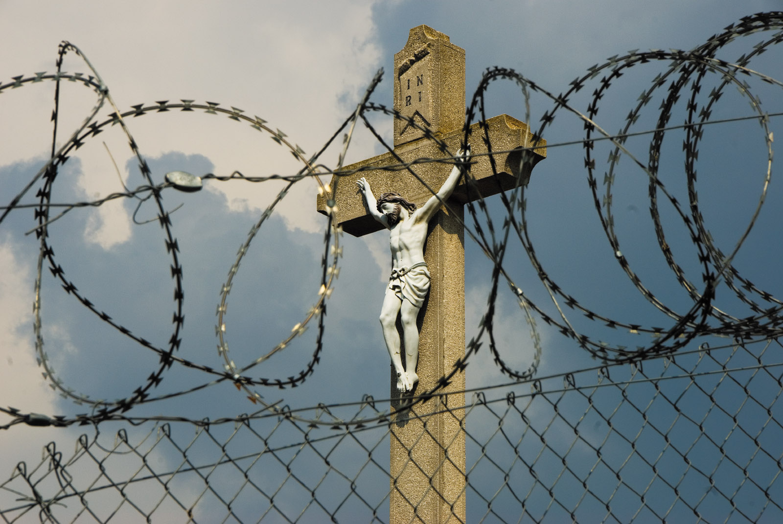 A Hungarian crucifix seen through the razor wire of the border fence, Rastina, Serbia, September 2016
