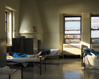 A shared room at the Bellevue Men's Shelter, housed since 1984 in the former psychiatric building of Bellevue Hospital, New York City, 2010; photograph by Eric Michael Johnson