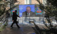 Vladimir Putin on screen delivering an annual news conference, in Simferopol, Crimea, December 23, 2016