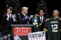 President-Elect Donald Trump holding a Green Bay Packers jersey during his 'Thank You Tour,' West Allis, Wisconsin, December 2016. With him are House Speaker Paul Ryan, Wisconsin Governor Scott Walker, and Vice President–Elect Mike Pence.