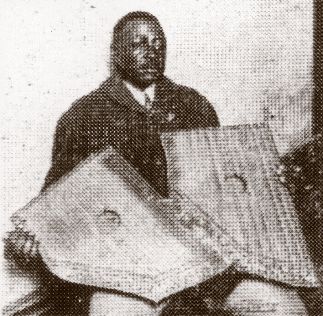 Phillips during a recording session, holding two zithers that seem to be attached, December 1927