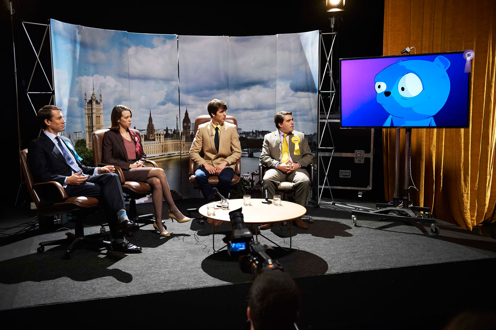 "Tobias Menzies as Liam Monroe, Chloe Pirrie as Gwendolyn, Jack Monaghan as Robert, Louis Waymouth as Simon Finch, and Waldo voiced by Daniel Rigby, in ""The Waldo Moment,"" <em>Black Mirror</em> Season 2, 2013"