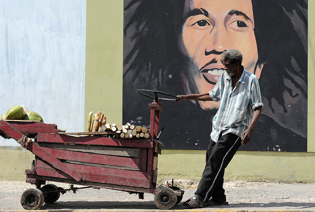 A vendor pulling his cart in front of a mural of Bob Marley, Kingston, Jamaica, February 8, 2009