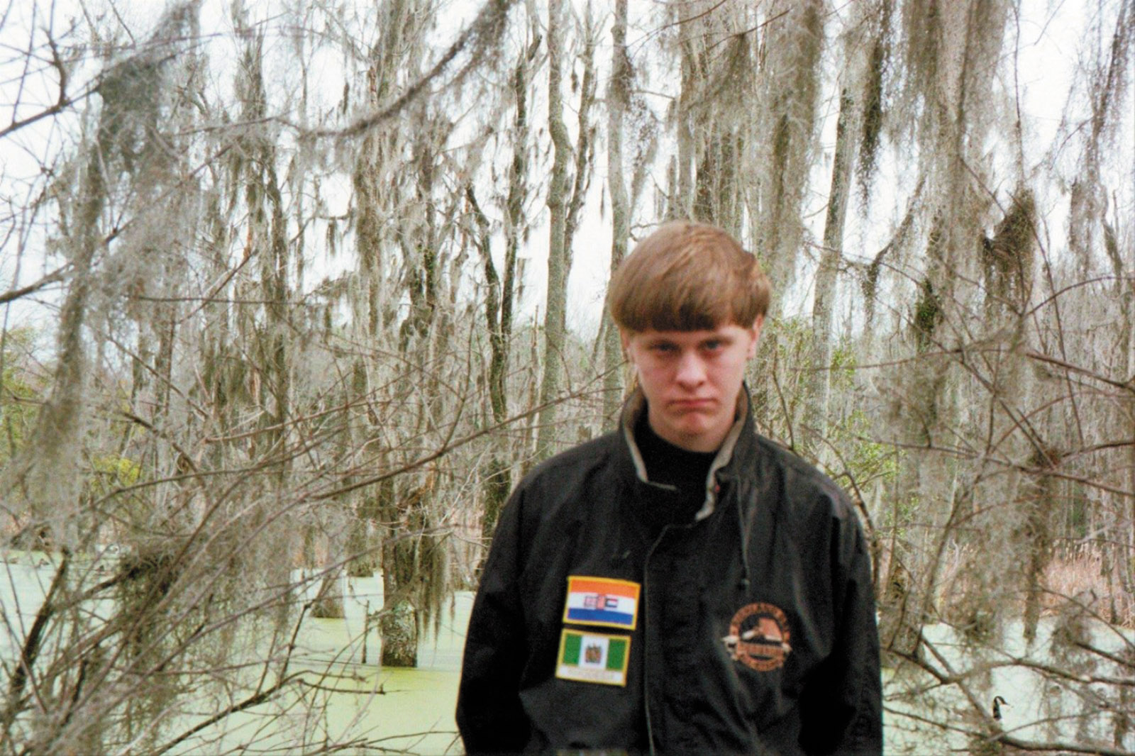 Dylann Roof wearing a jacket decorated with the flags of apartheid-era South Africa and white-ruled Rhodesia
