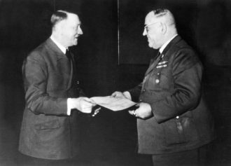 Adolf Hitler presenting Theodor Morell, his personal physician, with the Knight's Cross of the War Merit Cross at his headquarters, 1944