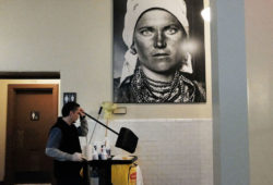 A custodian working under a portrait of an immigrant from the early twentieth century at Ellis Island, New York, January 31, 2017