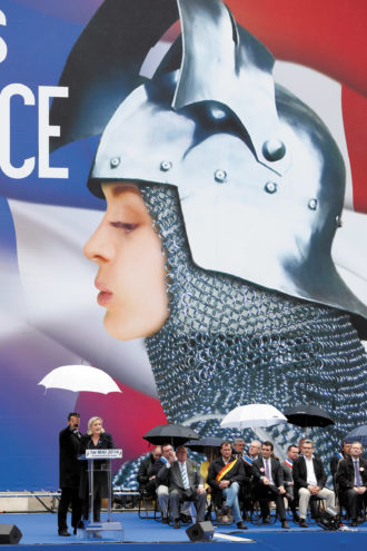 Marine Le Pen delivering a speech in front of a poster of Joan of Arc during the National Front's May Day rally, Paris, May 2014