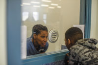 A mother talking with her son through a window at the Florida Women's Reception Center, a prison in Ocala, Florida, April 2016; photograph by Isadora Kosofsky from her series 'Still My Mother, Still My Father,' which documents parent–child visits in Florida prisons. An exhibition of her work will be on view at the Davis Orton Gallery, Hudson, New York, June 24–July 23, 2017.