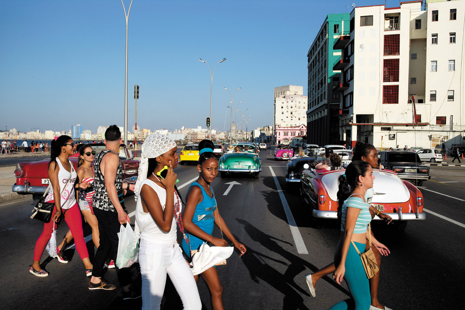 Young Cubans crossing the Malecón as tourists drive by in antique American convertibles, Havana, May 2016