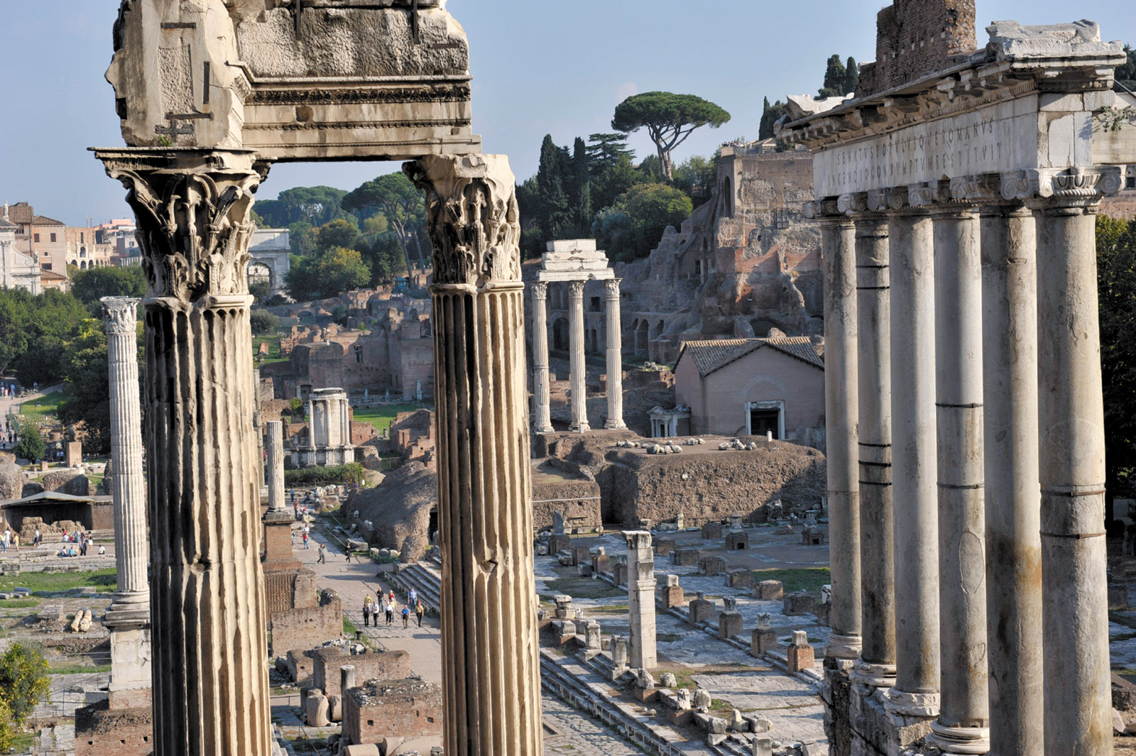 The Roman Forum in 2008, looking east toward the Arch of Titus, with the remains of the Temple of Saturn (right), the Temple of Castor and Pollux (center, with three columns), and the Temple of Vespasian (foreground); the Palatine Hill rises to the right