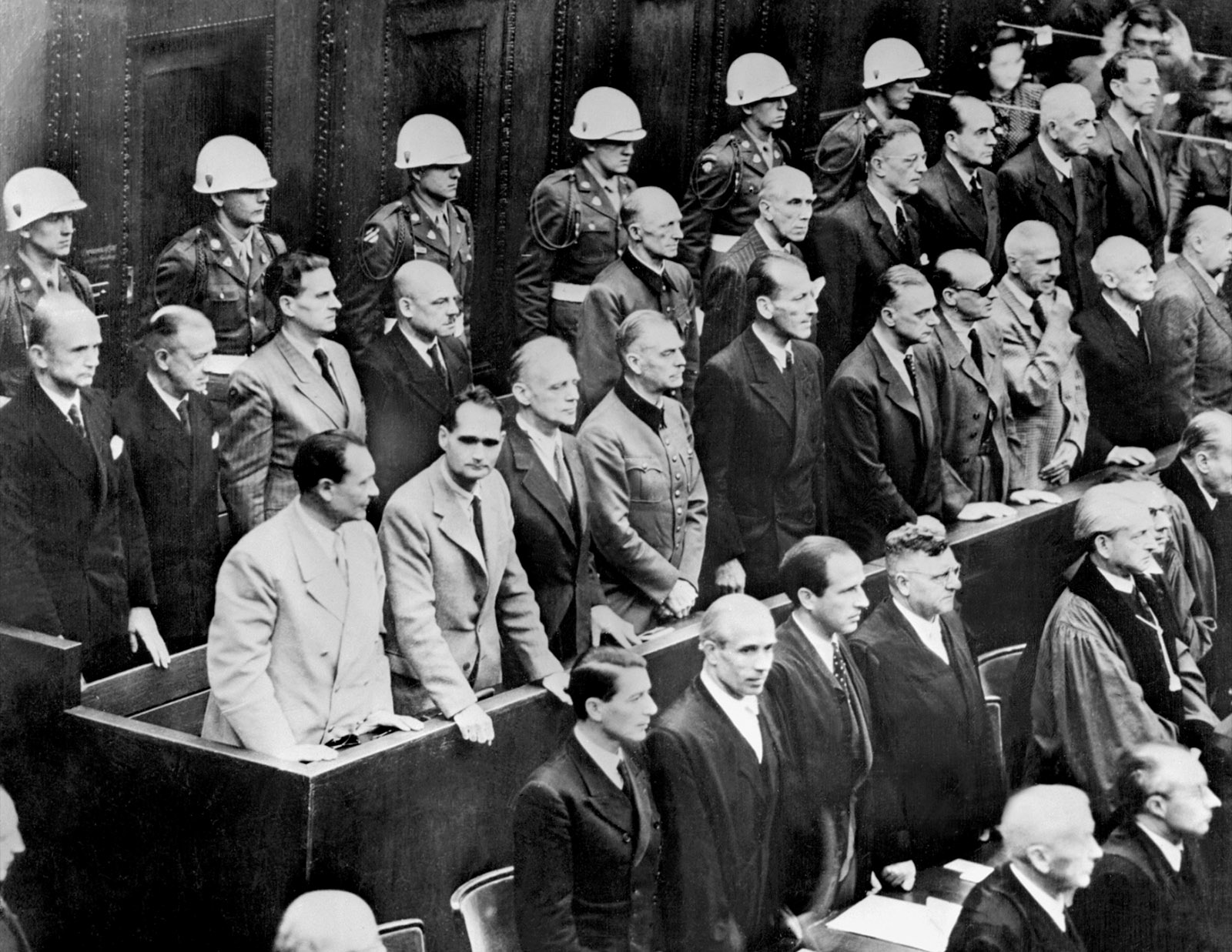 Nazi leaders accused of war crimes during World War II standing to hear the verdict in their trial, Nuremburg, October 2, 1946. Albert Speer is third from right in the back row of defendants; Karl Dönitz is at the far left of the same row.