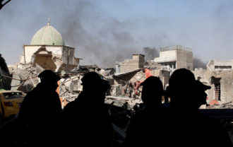 Members of Iraqi Counter Terrorism Service and the media standing before the ruins of the Grand al-Nuri Mosque, Mosul, June 29, 2017