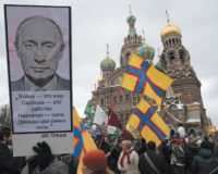 Protesters marching near the Church of the Savior on Spilled Blood, St. Petersburg, February 25, 2012. The poster on the left carries two slogans drawn from George Orwell's 1984: 'War is Peace, Freedom is Slavery, Ignorance is Strength,' and 'Two plus two equals five.'