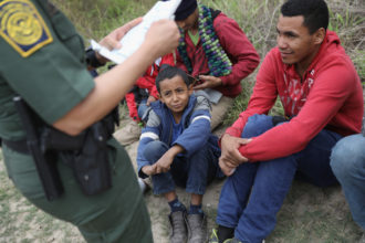 A US Border Patrol agent checking birth certificates while taking immigrants from Central America into detention, McAllen, Texas, January 4, 2017