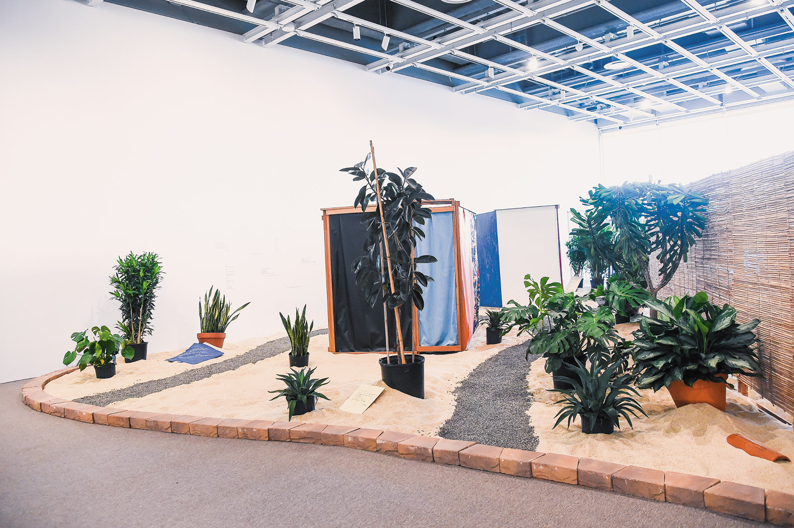 Hélio Oiticica: Tropicália, 1966–1967. The installation, on view at the Whitney, includes plants, sand, birds, and a poem by Roberta Camila Salgado inscribed on brick, tile, and wood.