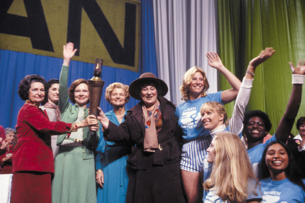 First Ladies Lady Bird Johnson, Rosalynn Carter, and Betty Ford, International Women's Year presiding officer Bella Abzug, and Torch of Freedom relay runners at the opening ceremonies of the National Women's Conference, Houston, November 1977