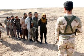 A member of the Kurdish peshmerga detaining ISIS militants, southwest of Kirkuk, Iraq, October 5, 2017
