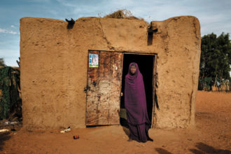 Noura, an elderly haratin woman in front of her house in the village of Tejala, Mauritania, 2013