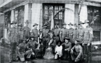 US soldiers who survived a surprise attack during the Philippine-American war posing with one of the bells of Balangiga, Philippines, 1901-1909