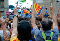 People gesturing at a giant screen broadcasting Spain's Prime Minister Mariano Rajoy, Barcelona, October 27, 2017