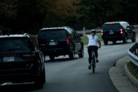 "Juli Briskman gesturing at President Donald Trump's motorcade, Sterling, Virginia, October 28, 2017. Briskman was subsequently fired by her employer over the incident but expressed no regret: ""I'm angry about where our country is right now.… This was an opportunity for me to say something."""