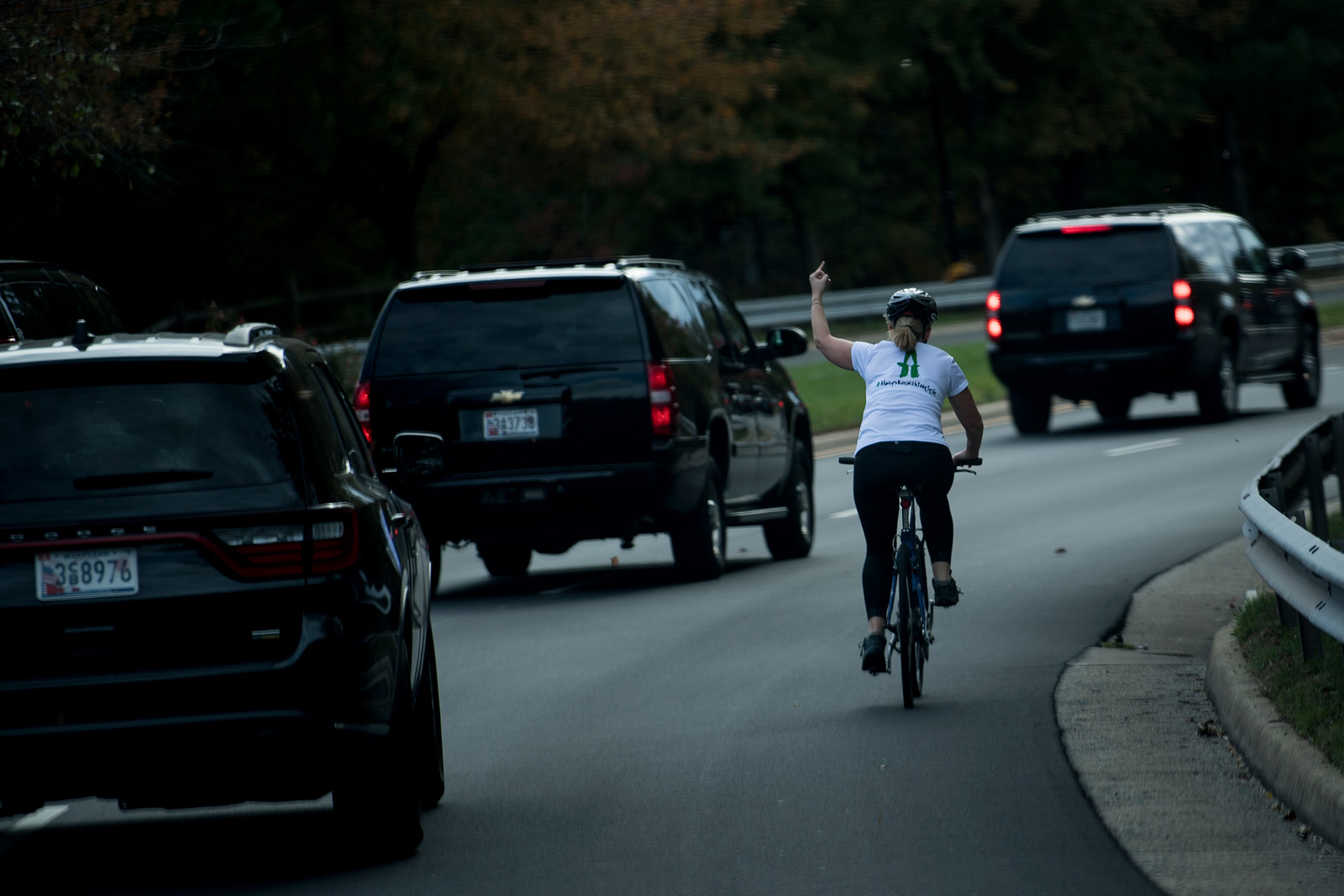 """Juli Briskman gesturing at President Donald Trump's motorcade, Sterling, Virginia, October 28, 2017. Briskman was subsequently fired by her employer over the incident but expressed no regret: """"I'm angry about where our country is right now.… This was an opportunity for me to say something."""""""